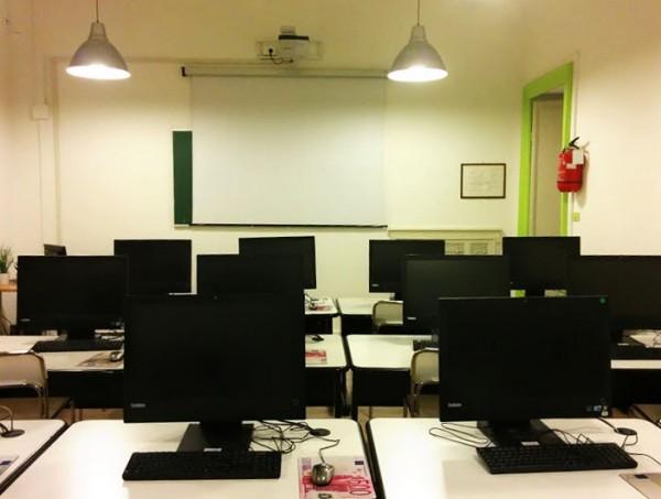 aula informatica con 12 postazioni collegate a Internet, lavagna tradizionale e proiettore a soffitto.